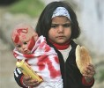 A Palestinian girl eats bread as she carries a doll wrapped in a symbolic shroud during a demonstration against Israel's military operation in Gaza